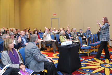Wendy Kobler engages seated participants some of whom raise their hands