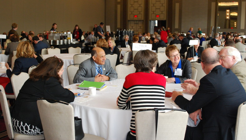 Participants eating breakfast and sharing ideas at roundtables with designated topics