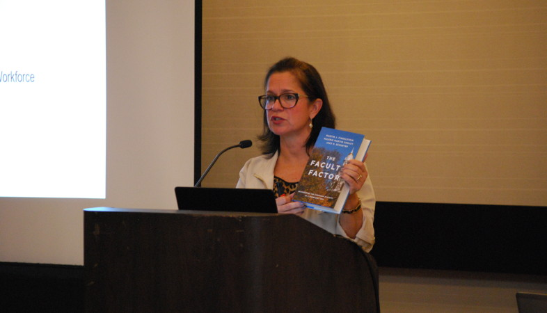 Anne Ollen presents from the podium holding a book