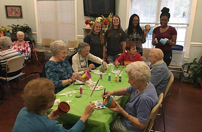 Students assist older adults with painting terracotta pots