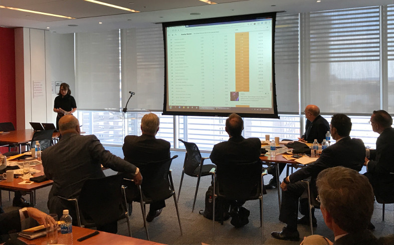 New York Times reporter speaks to group of seated college presidents in front of a projector screen displaying a graph