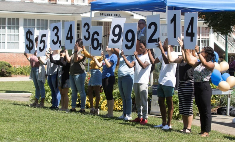 Students hold signs of numbers, representing the amount of money raised