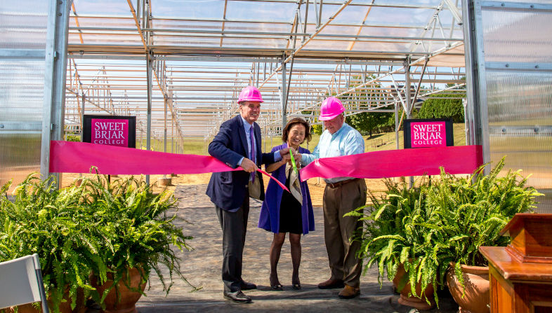 Three people cut a ribbon in front of new greenhouse