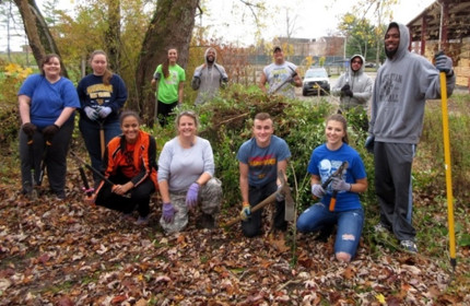 a group of students pose with gardening tools in front of collected leaves and debris