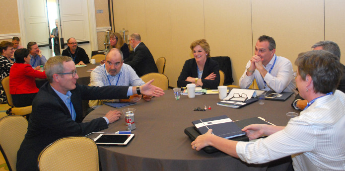 Participants seated at roundtables asking questions at a session