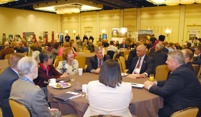 Participants discuss topics over breakfast seated at roundtables