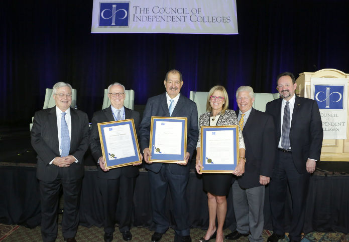 Richard Ekman and Thomas Hellie stand with the four awardees holding their framed awards