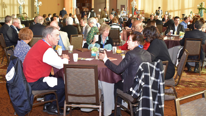 Participants seated at breakfast roundtables
