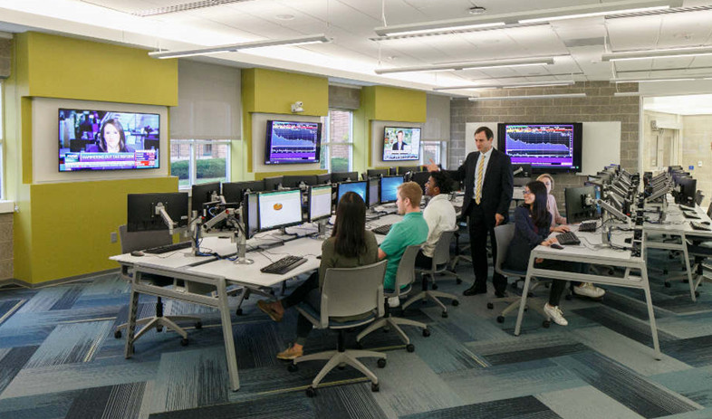 Professor instructs students who are seated at computer workstations and wall-mounted TVs display financial news and data.