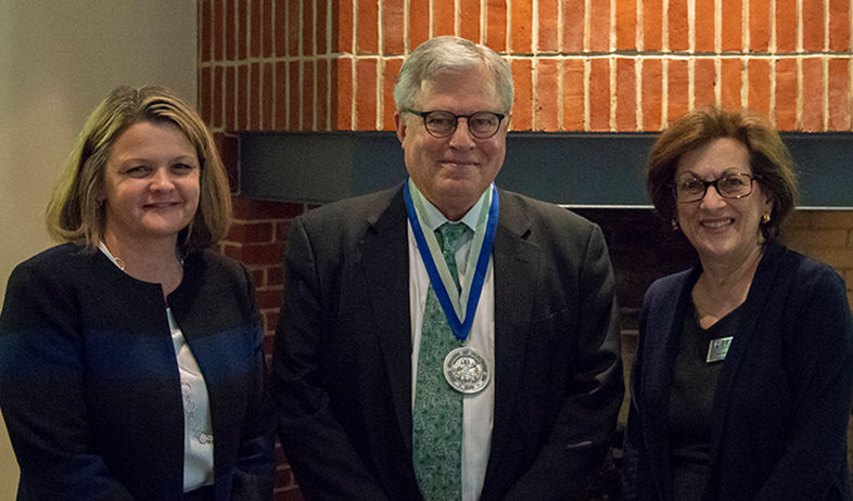 Richard Ekman wearing a medal stands between Hood College's president and board chair