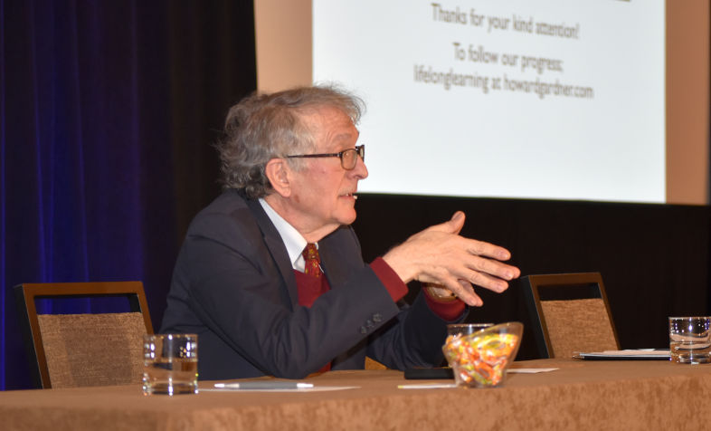 Howard Gardner presents while seated at a head table