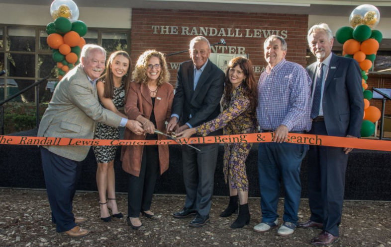 Seven people cut a ribbon in front of a new building