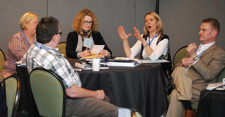Five participants share ideas at a roundtable discussion