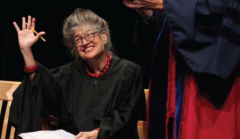 Helen Whitney waves while holding a pencil and wearing graduation robes