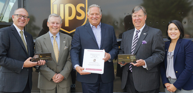 Representatives of UPS, Missouri Colleges Fund, and Lindenwood University pose in front of a UPS truck while holding two miniature UPS trucks and book of thank you letters from UPS Scholarship recipients.