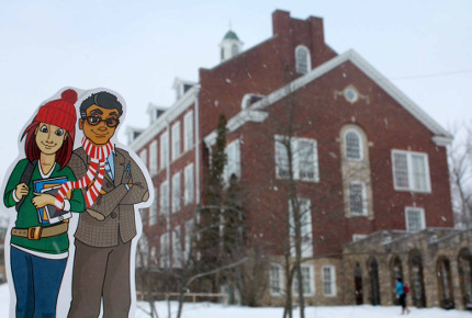 Libby and Art are wearing a scarf and hat in front of a campus building in the snow