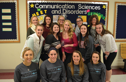 Group of female students pose in front of a Communication Sciences and Disorders bulletin board