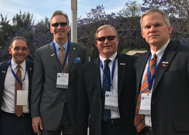Four American college presidents stand for photo wearing name badges around necks