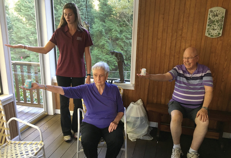 A student demonstrates balancing a paper cup on her outstretched hand to two older adults