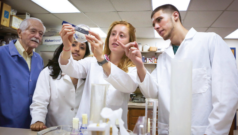 Three students in lab coats measuree a sample with a professor