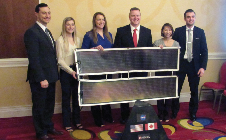 Team members stand with their flexible solar panels