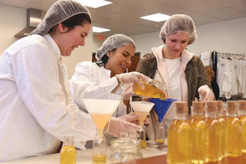 three students fill jars with honey