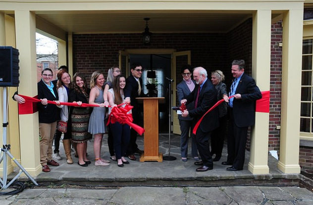campus officials dedicate a new building by cutting a red ribbon across the entrance