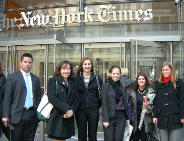 College students in business attire stand in front of The New York Times office