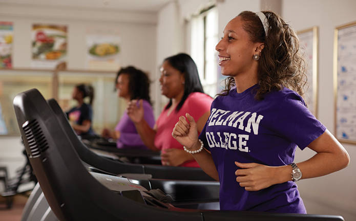 Four students running on treadmills