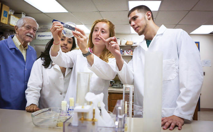 Three students in lab coats are observed by a professor