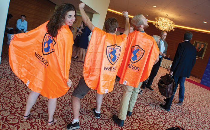 three students wearing Watson Institute ponchos
