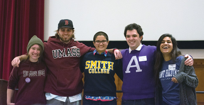 Five students from five colleges pose while wearing their college shirts