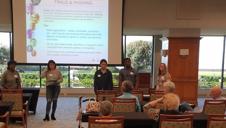 Five students present to seated audience of older adults on fraud and phishing.