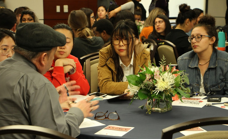 Older adult speaks with four students seated at a roundtable