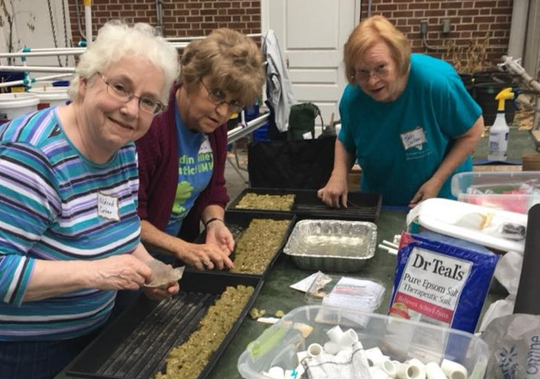 Three older adults prepare for a garden project