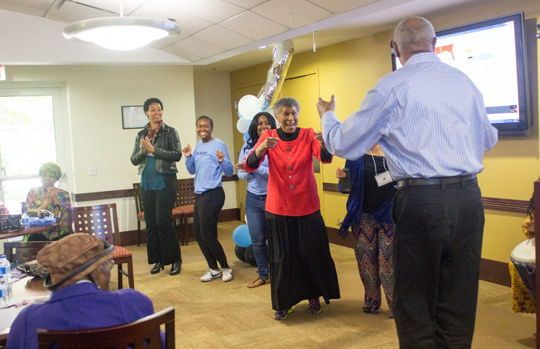 Students and older adults dance for seated older adults